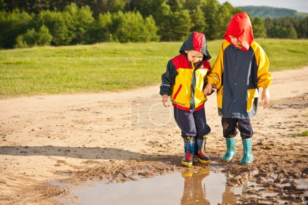 Two boys walking through a mud puddle