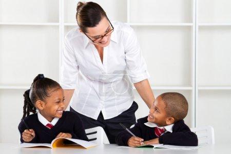 Elementary teacher talking to pupils