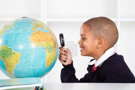 Primary schoolboy looking at globe