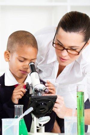 Beautiful young teacher helping school boy