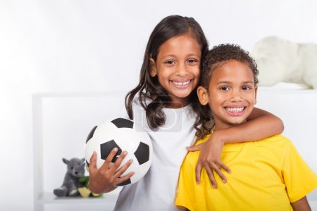 Brother and sister holding a soccer ball