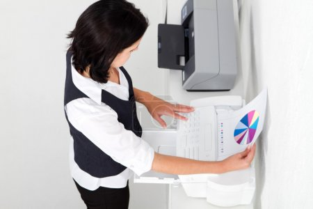 Businesswoman using fax machine in office