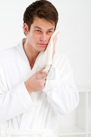 Young man wash face with a towel