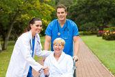 Starostlivý lékař, zdravotní sestra a starší pacient venku
