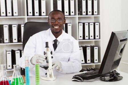 African american medical scientist with microscope in laboratory