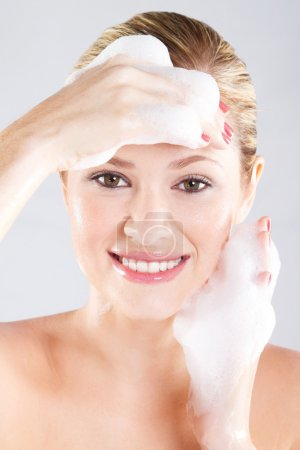 Young woman washing her face with foam