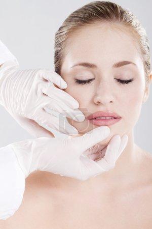 Photo pour Médecin de vérifier les lèvres de la femme avant la chirurgie esthétique - image libre de droit