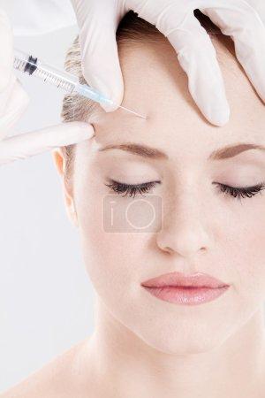 Docteur injection donne sur le front de la femme