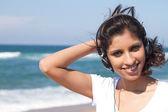 Young Arabian woman listening music on beach