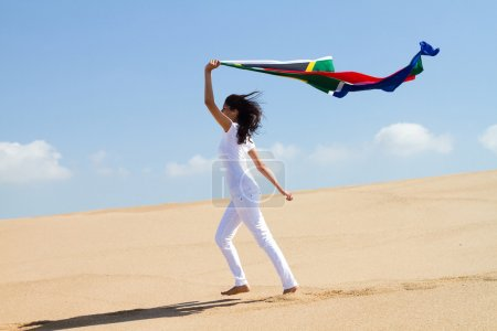 Young woman running on beach with south african flag