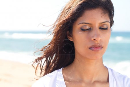 Thoughtful young indian woman with eyes closed on beach