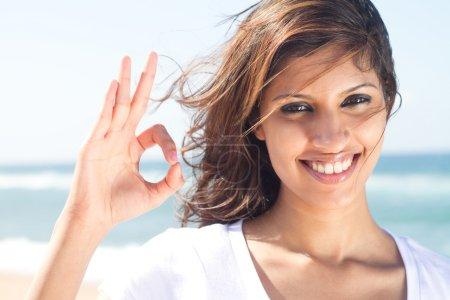 Woman giving ok hand sign on beach