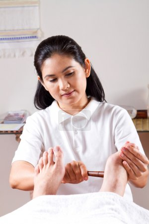 Photo pour Massage des pieds donnant de masseuse asiatique dans le centre de bien-être - image libre de droit
