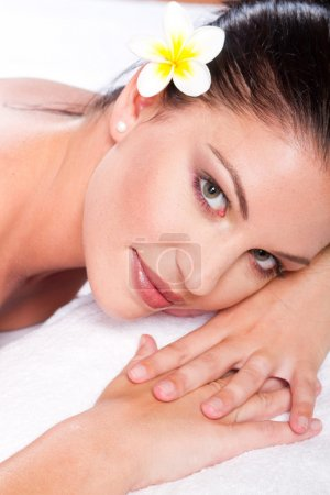 Beautiful happy young woman with flower in spa