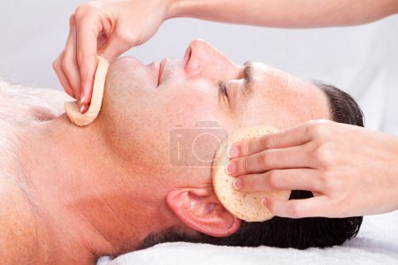 Middle age man receiving facial massage
