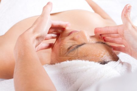 Woman receiving honey facial massage