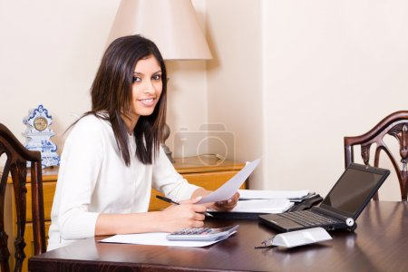 Woman at home sorting financial papers