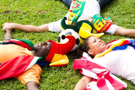 Group of soccer fans lying on grass