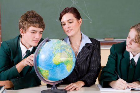 Photo for High school teacher and students viewing globe in geography classroom - Royalty Free Image
