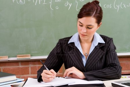 Photo for Pretty female school teacher preparing lesson in classroom - Royalty Free Image