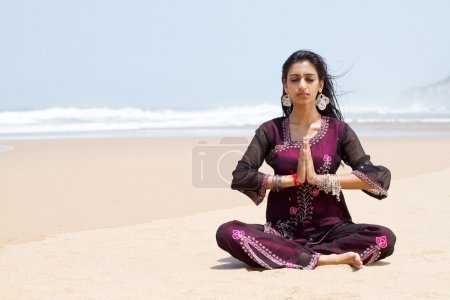 Indian woman in traditional clothing on beach meditation
