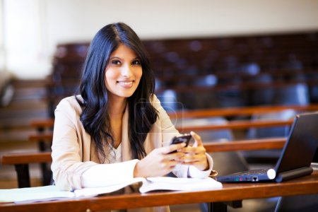 College student in lecture hall with mobile phone