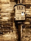 Vintage taxi sign on brick wall