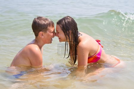 Happy brother and sister swim in the sea...