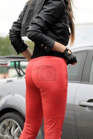 Legs female model posing near car