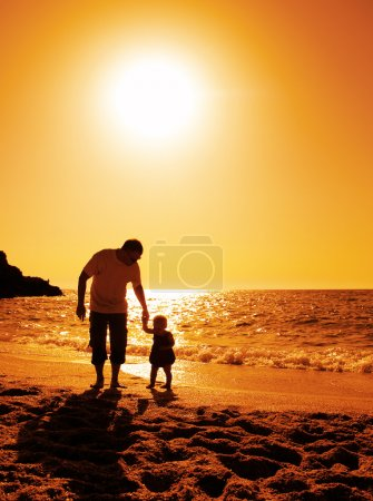 Photo for Father and daughter playing on the beach at sunset - Royalty Free Image