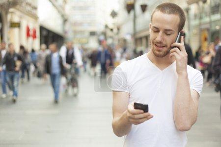 Photo pour Hommes tenant en mains deux GSM, rue de la ville et en arrière-plan - image libre de droit