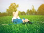 žena leží na trávě