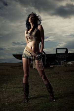 Photo for Dark sombre portrait of a beautiful sexy shapely woman in skimpy shorts with a bare midriff and boots posing under a stormy overcast sky - Royalty Free Image