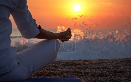 Photo for Woman Practicing Yoga near the Ocean at Sunset - Royalty Free Image