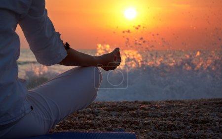 Photo pour Femme pratique l'yoga près de l'océan au coucher du soleil - image libre de droit