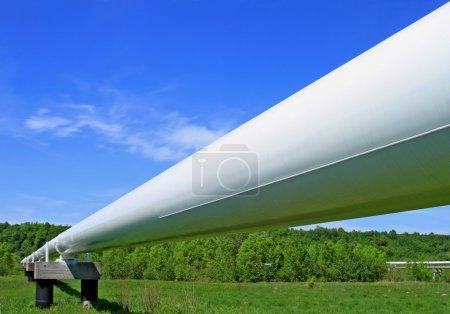 Photo pour Le pipeline haute pression dans un paysage estival avec le ciel bleu foncé et les nuages - image libre de droit