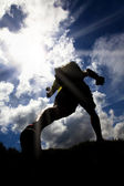 The Silhouette of runner on the grass field with sunlight background