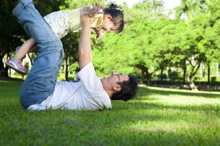 Happy father and little girl on the grass
