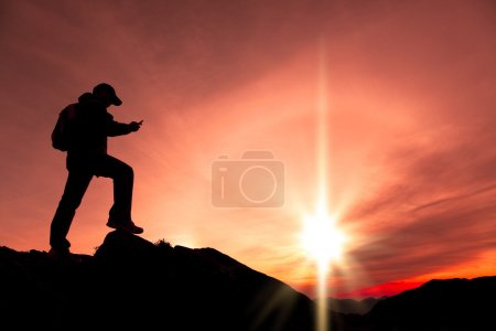 Photo for Young man using smart phone on the top of mountain - Royalty Free Image