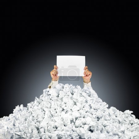 Photo for Person under crumpled pile of papers with hand holding a help sign - Royalty Free Image
