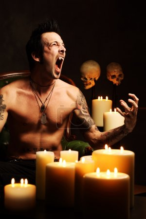 Photo pour Photo d'un vampire mâle reposant sur une chaise en cuir et crocs montrant. Éclairage dur et sombre pour une sensation plus effrayante . - image libre de droit