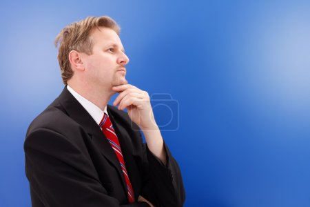 Photo for Serious business man thinking, blue copy space in front of him - Royalty Free Image