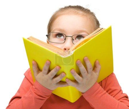 Photo pour Petite fille mignonne avec des lunettes noires rêve tout en lisant le livre, isolé sur blanc - image libre de droit