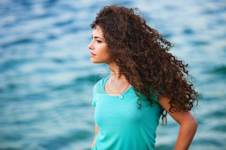 Photo pour Portrait de jeune femme avec une journée venteuse de long cheveux bouclés par l'heure d'été mer - image libre de droit