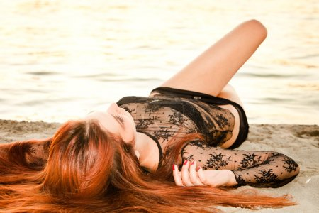 Photo for Young redhead woman lie on sand beach summer day - Royalty Free Image