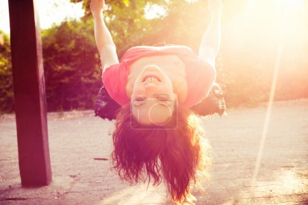 Photo for Happy teen girl have fun on swing sun flare - Royalty Free Image