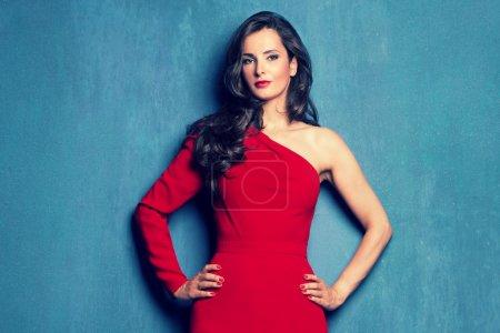 Photo pour Belle femme élégante dans une robe rouge avec un manchon sur mur bleu studio tourné - image libre de droit