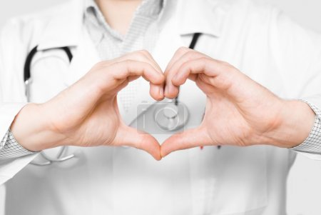 Young doctor with heart shaped fingers on white background