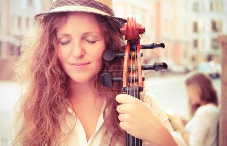 Photo for Portrait of street musician woman with cello closed eyes. Split toning - Royalty Free Image