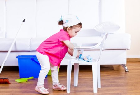 Photo for Little girl wiping dust off a kid chair - Royalty Free Image